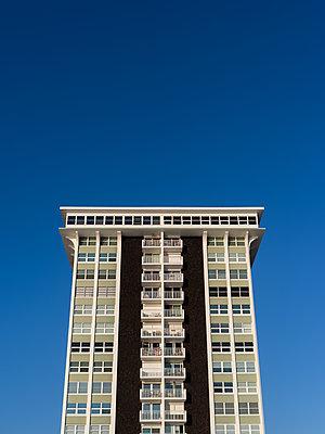 Apartment building against blue sky - p1335m1586374 by Daniel Cullen