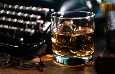 Whiskey glass next to typewriter on desk - p1427m2213527 by Tetra Images