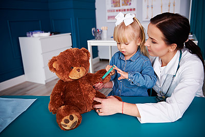 Doctor and girl vaccinating teddy in medical practice - p300m1567658 by gpointstudio