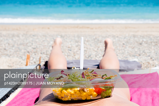 Man lying down on the beach with a salad in a plastic container in his back - p1423m2099175 von JUAN MOYANO