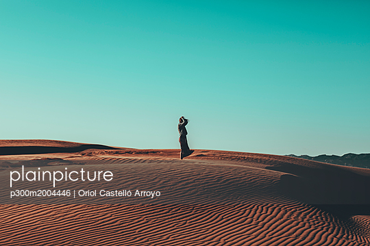 Young woman with windswept hair standing in desert landscape - p300m2004446 von Oriol Castelló Arroyo