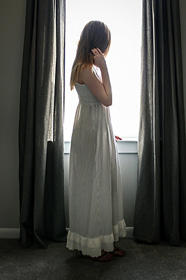 Young woman looking out of window - p1019m2073368 by Stephen Carroll