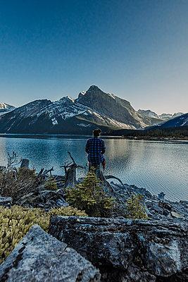 Junge Frau sitzt vor einem See mit Berge im Hintergrund - p1455m1574491 von Ingmar Wein