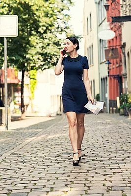 Young woman on cell phone walking in the city - p300m1189024 by A. Tamboly