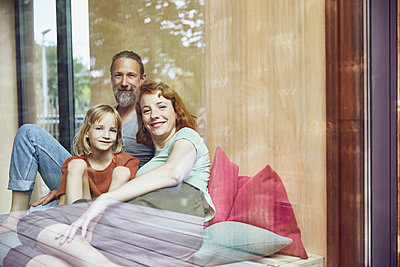 Smiling family relaxing on bed at home seen through window - p300m2214032 by Maya Claussen