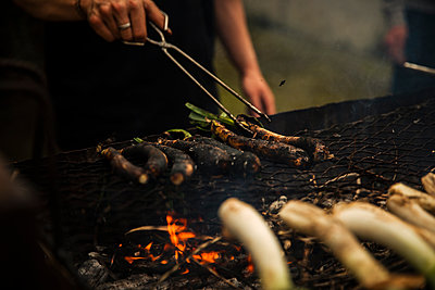 Teenage boy using serving tongs while cooking Scallions on barbecue grill standing outdoors - p300m2264410 by Aitor Carrera Porté
