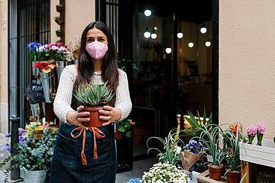 Valencia, Spain. Woman working in a florist's shop with a mask standing in the doorway of her shop. - p300m2274212 von Ezequiel Giménez