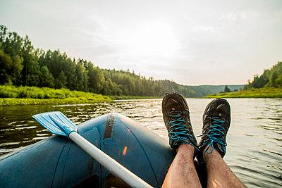 Man resting feet on boat in lake - p555m1420556 by Aleksander Rubtsov