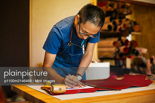 Japanese man wearing blue apron working in a leather shop. - p1100m2146468 by Mint Images