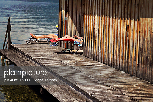 Couple sunbathing near a swimming lake in Austria  - p1540m2175069 by Marie Tercafs