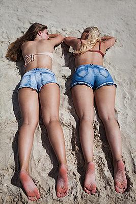 Zwei junge Frauen liegen nebeneinander im Sand - p045m2021899 von Jasmin Sander