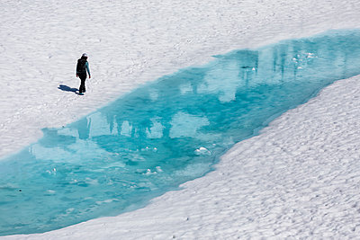 Drone view of unrecognizable female hiker walking along melting lake with clear blue water during vacation in British Columbia - p1166m2208547 by Cavan Images