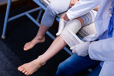 Doctor putting bandage on injured leg of patient - p1315m1230787 by Wavebreak