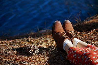 Legs of the woman relaxing next to the lake - p1577m2175343 by zhenikeyev