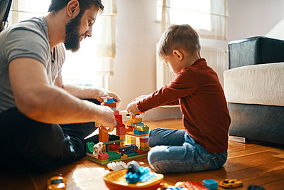Father and son sitting on the floor  playing together with building bricks - p300m1581075 by Zeljko Dangubic