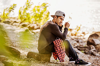 Young man wearing baseball cap sitting in nature - p300m2005586 von Jan Tepass