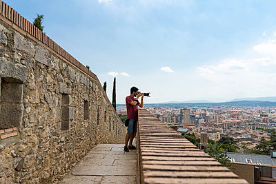 Spain, Girona, man at the castletaking picture of the city - p300m2012334 von VITTA GALLERY