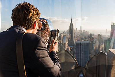 USA, New York City, man looking through coin-operated binoculars on Rockefeller Center observation deck - p300m2013081 by Uwe Umstätter