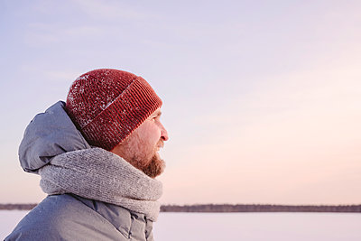 Mid adult man wearing warm clothing looking against sky during sunset - p300m2265156 by Ekaterina Yakunina