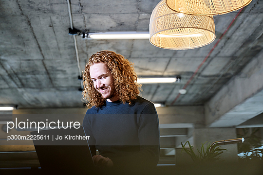 Smiling redhead man using laptop at home - p300m2225611 by Jo Kirchherr