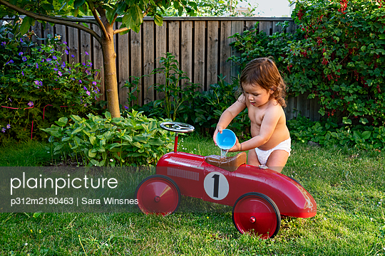 Toddler girl pouring water over ride-on car - p312m2190463 by Sara Winsnes
