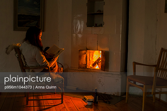 Young woman sitting by fire - p956m1044373 by Anna Quinn