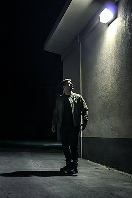 Man in a street at night - p1019m1424634 by Stephen Carroll