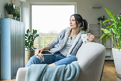 Pensive woman with a mug and tablet sitting on the couch at home - p300m2104569 by Uwe Umstätter