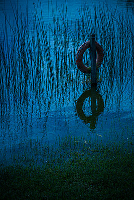 Life preserver hanging on wooden post at water's edge - p675m1063054 by Frederic Cirou