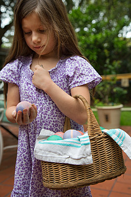 Girl carrying basket of dyed easter eggs in garden - p924m1224731 by Kinzie Riehm