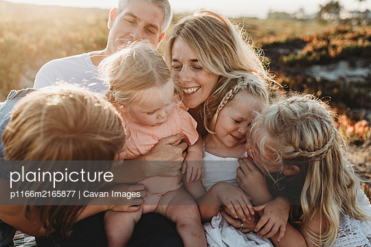 Lifestyle close up of family with young sisters sitting on beach - p1166m2165877 by Cavan Images