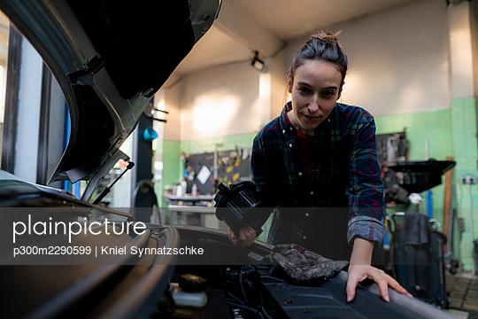 Female mechanic repairing car at workshop - p300m2290599 by Kniel Synnatzschke