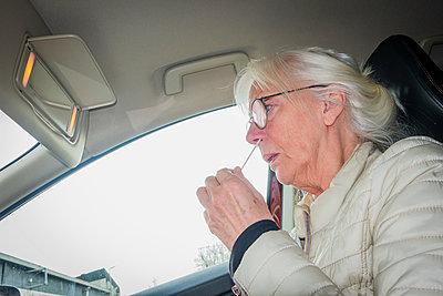 Woman taking drive-in test for covid-19 - p1418m2257910 by Jan Håkan Dahlström