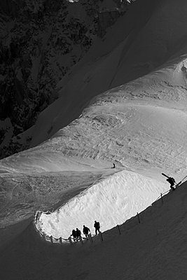 Skiers are walking down the steep ridge at Aiguille du midi to go skiing - p3433632 by Patrik Lindqvist