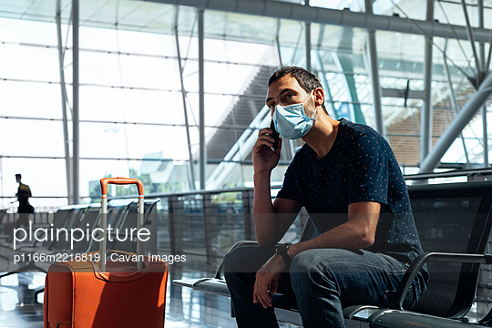 Young man wearing a face mask talking on the phone at the airport - p1166m2216819 by Cavan Images
