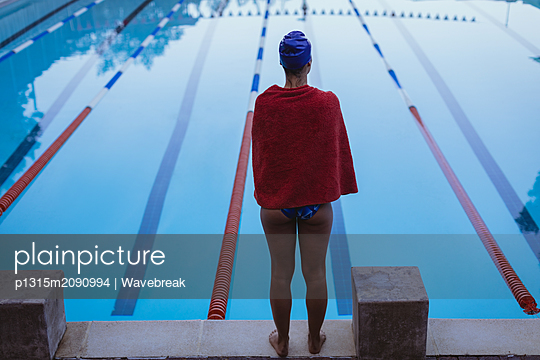 Young female swimmer wrapped in towel standing near swimming pool - p1315m2090994 by Wavebreak