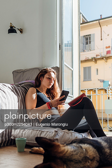 Woman using mobile phone while sitting with dog in bedroom - p300m2294043 by Eugenio Marongiu