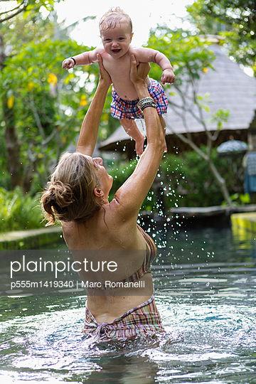 Caucasian mother and baby playing in pool - p555m1419340 by Marc Romanelli