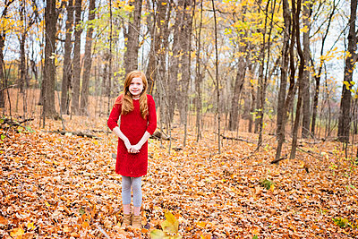 Young Red Hair Girl Playing Outside in Fall Leaves - p1166m2147097 by Cavan Images