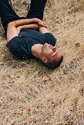 Man Resting in Withered Grass - p1262m1087717 by Maryanne Gobble