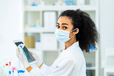 Female researcher with test tube and digital tablet in laboratory - p300m2265519 by Giorgio Fochesato