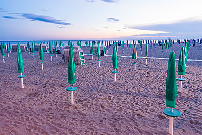 Italy, Friuli-Venezia Giulia, closed beach umbrellas on the beach of Grado - p300m975447f by Karl Thomas