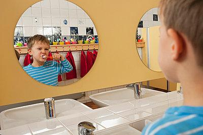 Germany, Boy (4-5) brushing his teeth in front of mirror, portrait - p300m981379f by Robert Niedring
