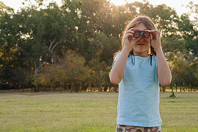 Girl looking through binoculars - p4297050 by Clarissa Leahy