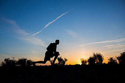 Silhouette of Caucasian teenage boy running at dawn - p555m1311603 by Mike Kemp