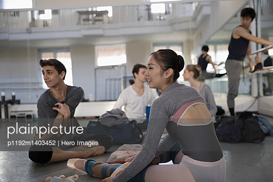 Ballet dancers stretching, warming up in dance studio