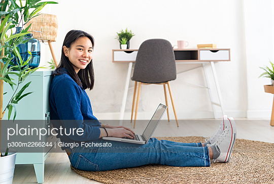 Young smiling woman with laptop sitting on jute rug at home - p300m2266244 by Giorgio Fochesato