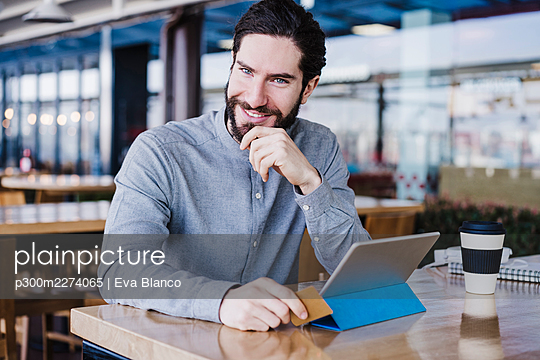 Smiling male entrepreneur with digital tablet and credit card at work place - p300m2274065 by Eva Blanco
