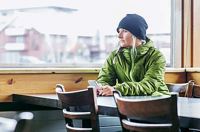 Woman looking away while sitting in cafe with smart phone - p1166m1172931 by Cavan Images