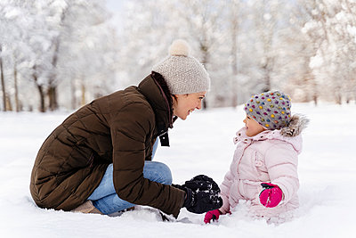 Happy mother playing with daughter in winter landscape - p300m2083150 by Daniel Ingold